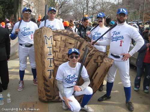 protestors stand near a huge baseball Mitt and wear baseball uniforms with the words Tax Dodgers and 1 percent on them