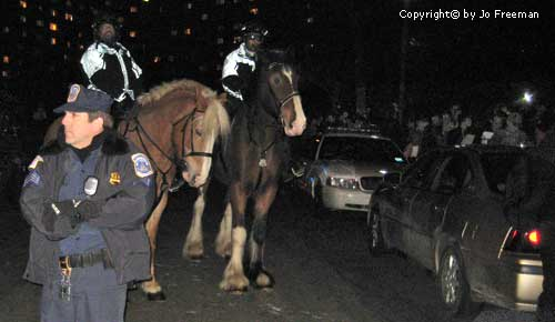 protestors stand near two police on horses and a third policeman standing in the foregraound